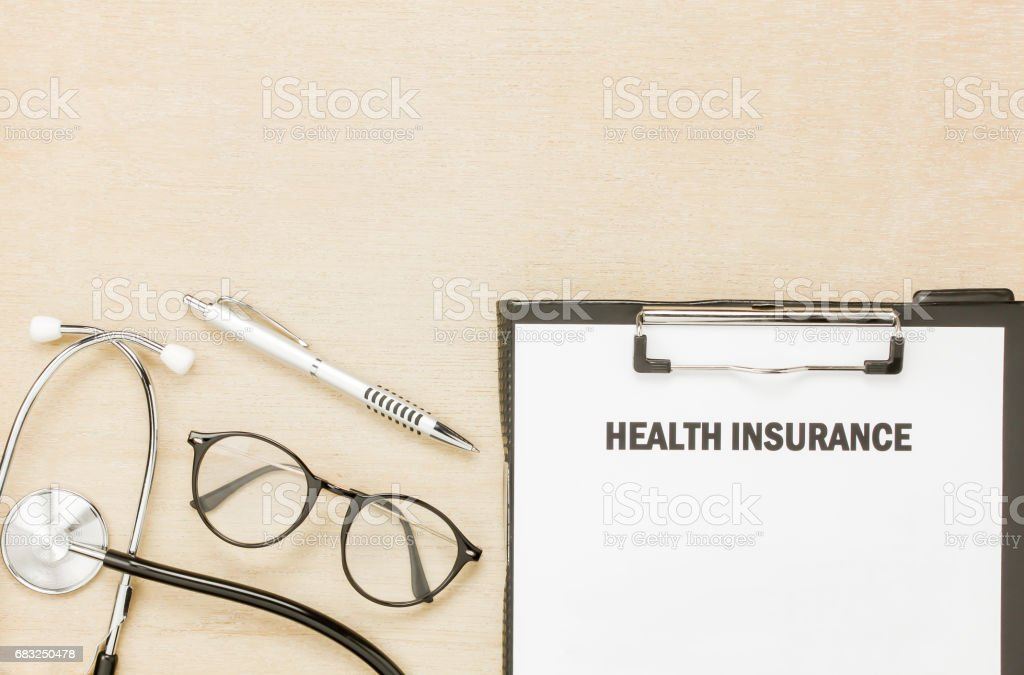 Top view health insurance form and eyeglasses with stethoscope on wooden background. royalty-free stock photo