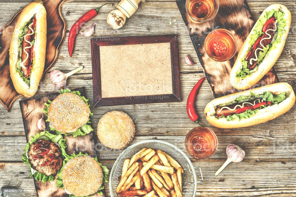 top view homemade burgers with beef, hot dogs and beer on a wooden table. Rustic style royalty-free stock photo
