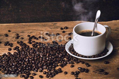 Top view Hot black coffee on a old kitchen table. background concept Coffee cup and and coffee beans on wooden table. Coffee beans spread on the table.