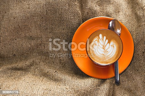 istock Top view hot latte in orange cup with floral pattern in foam on burlap background 909680776