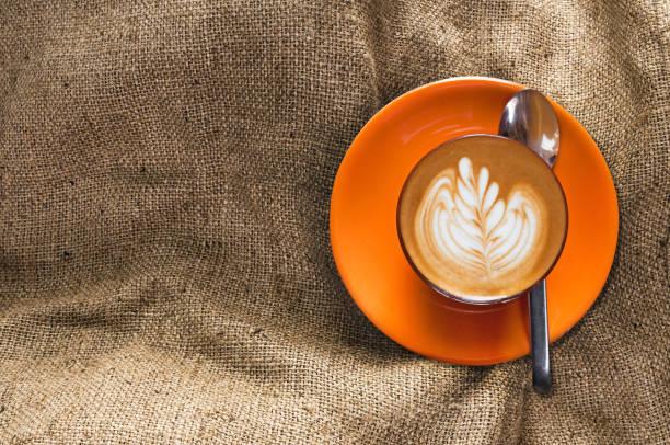 ansicht von oben heißen latte in orange schale mit blumenmuster in schaum auf sackleinen hintergrund - arten stock-fotos und bilder