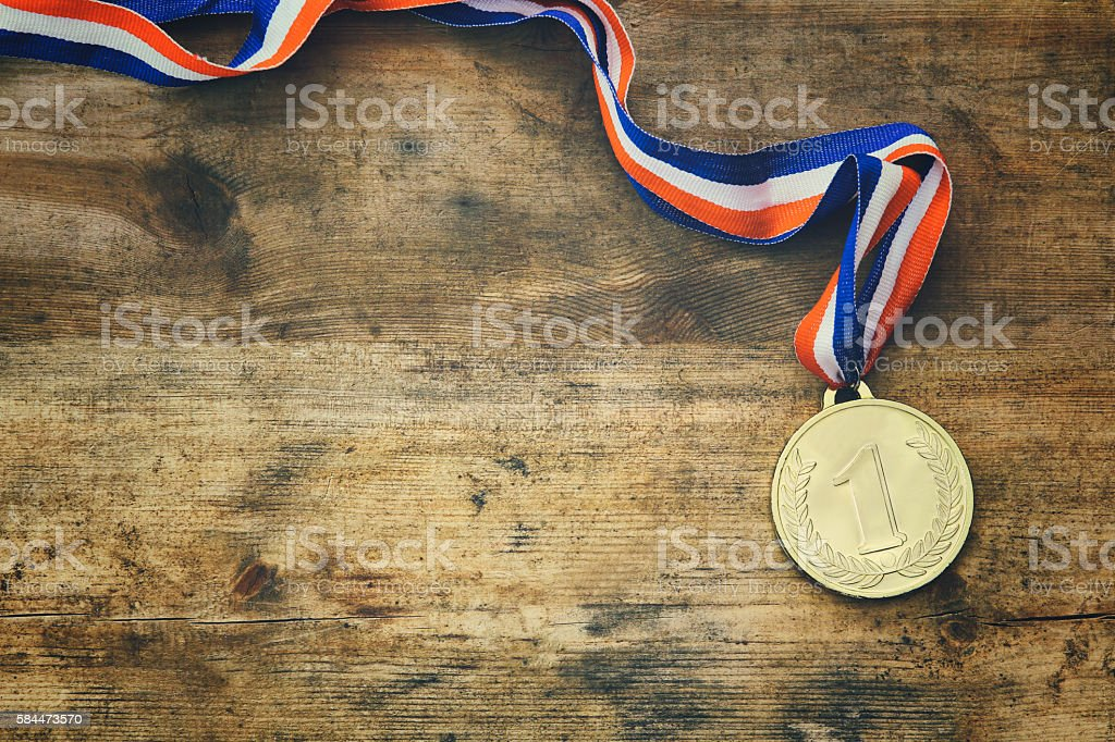 top view image of gold medal over wooden table stock photo