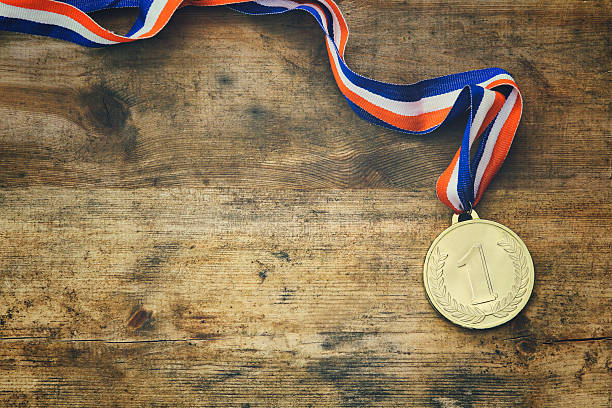 top view image of gold medal over wooden table - medal stock photos and pictures