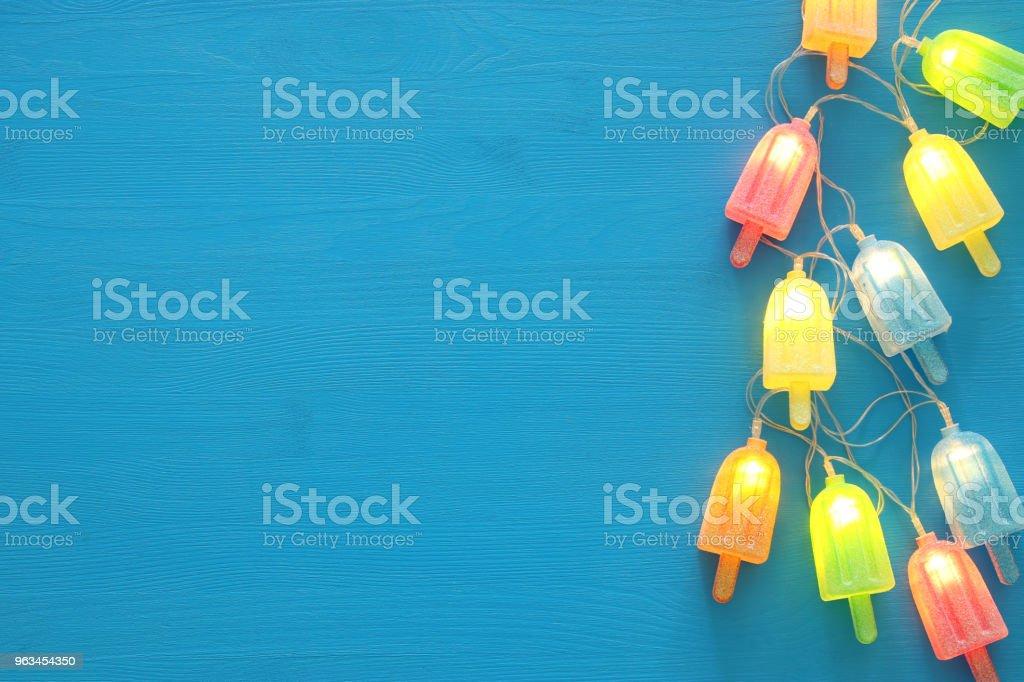 Üstten görünüm görüntüsünü ahşap mavi arka plan üzerinde dondurma sevimli parti garland ışıkları. - Royalty-free Aydınlık Stok görsel
