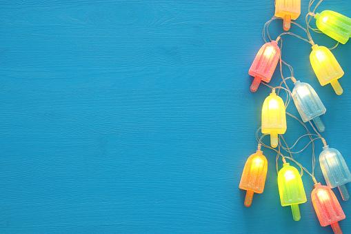 Üstten Görünüm Görüntüsünü Ahşap Mavi Arka Plan Üzerinde Dondurma Sevimli Parti Garland Işıkları Stok Fotoğraflar & Aydınlık'nin Daha Fazla Resimleri