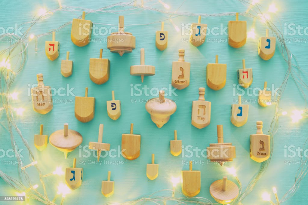 Top view Image of jewish holiday Hanukkah with wooden dreidels...