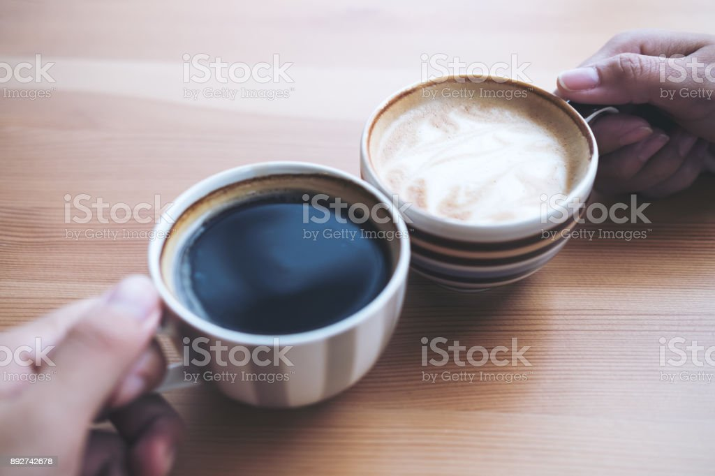Top view image of man and woman's hands holding coffee cups with wooden table background stock photo