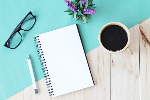 istock Top view image of open notebook with blank pages and coffee cup on wooden background, ready for adding or mock up 696186270