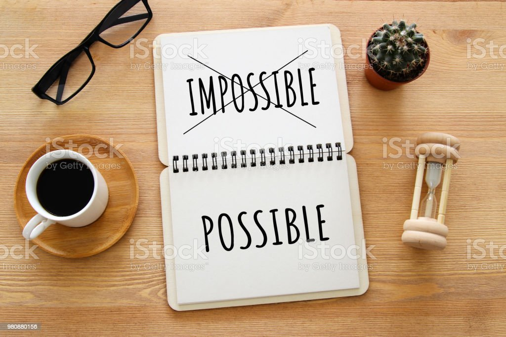 top view image of open notebook with the text impossible, cutting the word im so it written possible. success and challenge concept. retro style image. stock photo