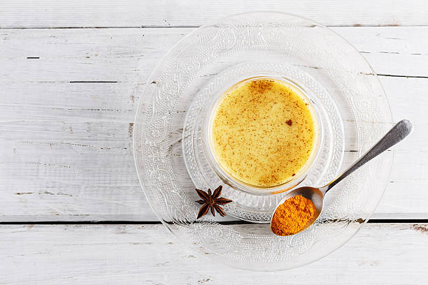 Top view image of turmeric latte over white wooden table stock photo