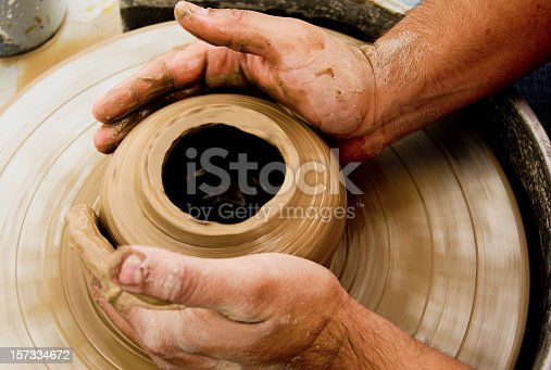 Person olding  jar of clay