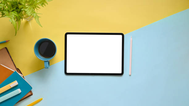 Top view image of workspace with flat lay white blank screen computer tablet, coffee cup, stylus pen, marker pens, stack of notebook and potted plant on colorful working table. stock photo