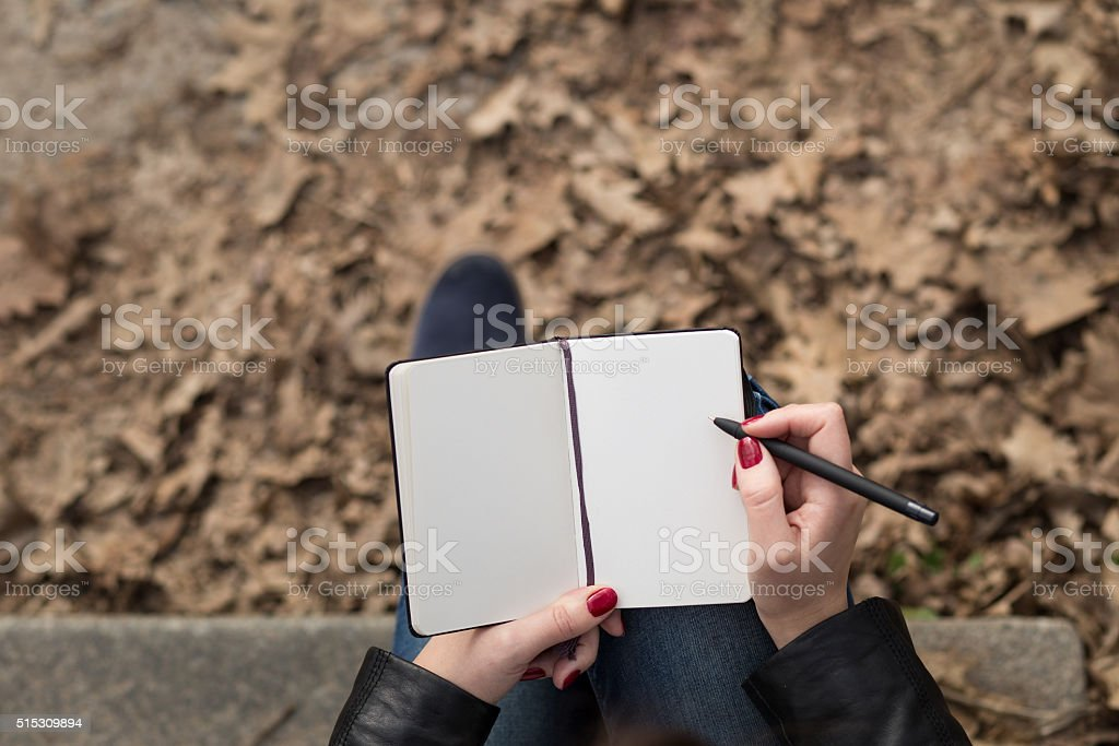 Top view image of open pad in feamle hands with pen sitting on stairs...