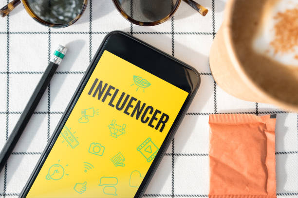 top view influencer feature on mobile screen with coffee cup,sunglasses,pencil on white table cloth.blogger lifestyle - influencer стоковые фото и изображения