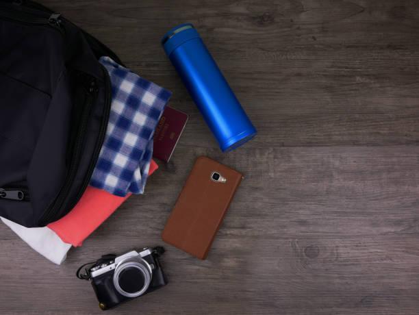 Vista superior itens para roupas de viagem incluída no saco preto, garrafa de água azul, celular e câmera em plano de fundo de madeira - foto de acervo