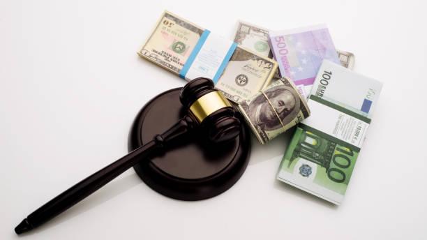 top vista el mazo del juez y paquetes de dólares y billetes en euros sobre un fondo blanco - indemnización compensación fotografías e imágenes de stock