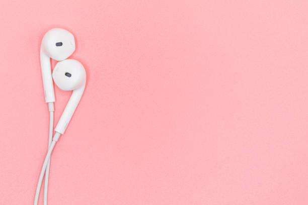 vue de dessus closeup belle des écouteurs blancs sur fond de texture en plastique rose pastel. concept de couleur pastel, notion minimale. copiez l'espace. la musique est mon concept de vie. concept de la saint-valentin - écouteurs intra auriculaires photos et images de collection