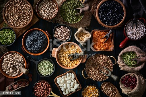 Variation of all kind of beans in rustic pots on a wooden table: Black beans, red beans, white beans, fabes, broad beans, alluvia chick-pea, green lentil, black lentil, orange lentil, kidney bean, black-eyed pea, green pea, corn, adzuki bean, lima bean, mung bean, pinto bean and split bean,