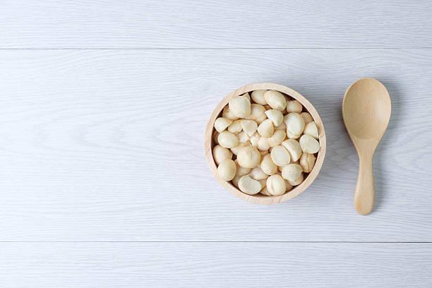 Vista superior macadamias y vacía en tazón de madera - foto de stock