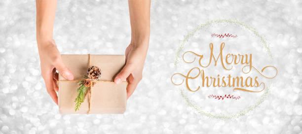 draufsicht frohe weihnachten kranz und hand mit xmas präsentieren feld mit silbernen glanz bokeh hintergrund, banner-grußkarte, geschenke auf saisonale ferienkonzept - bastelkarton stock-fotos und bilder