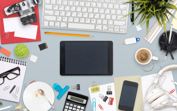 top view messy office desk header Overhead image of messy home office desk hero header with tablet and smartphone for responsive design mockup messy home office stock pictures, royalty-free photos & images
