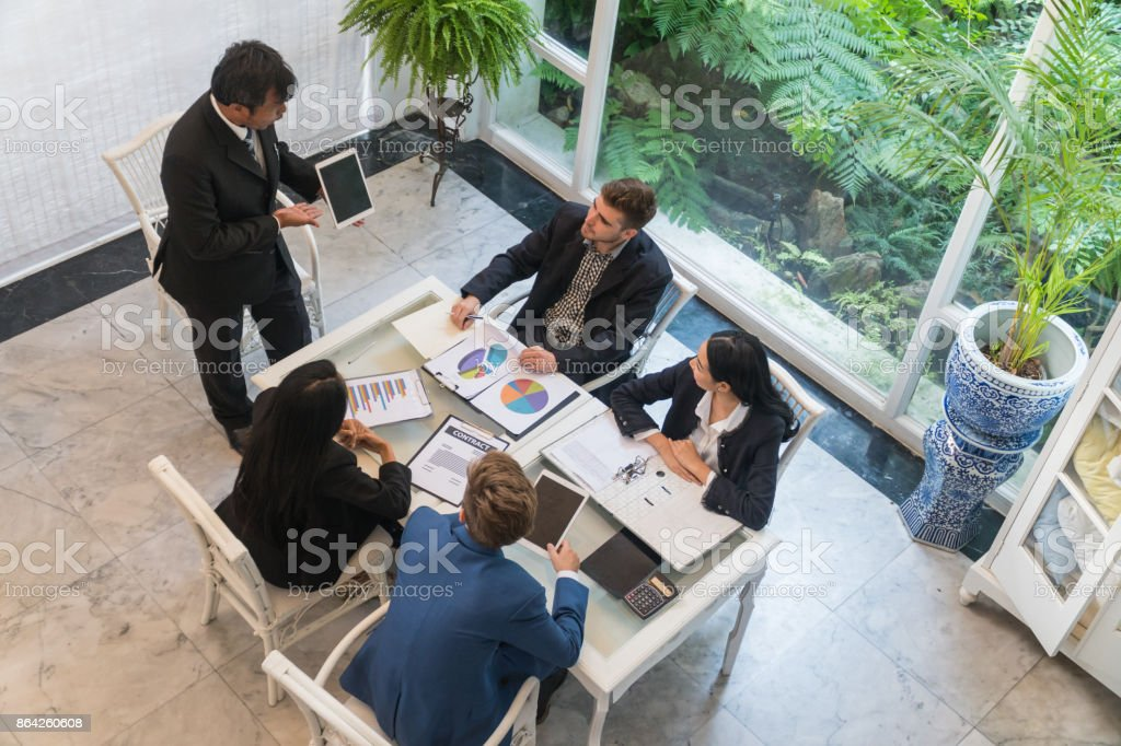 Top view Middle-aged businessman is presenting to a group of business people meeting. royalty-free stock photo