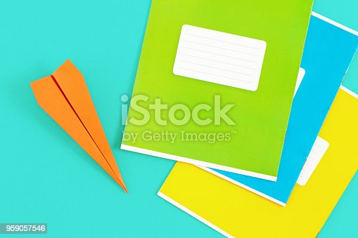 istock Top view minimalist education background. Set of colorful notebooks with paper airplane on blue background 959057546