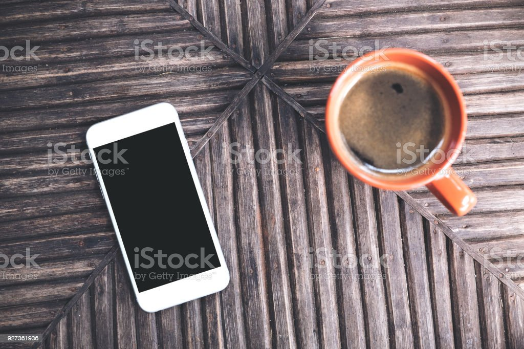 Top view mockup image of a white mobile phone with blank black desktop screen and a cup of coffee on vintage wooden table background - Royalty-free Above Stock Photo