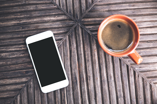 Top View Mockup Image Of A White Mobile Phone With Blank Black Desktop Screen And A Cup Of Coffee On Vintage Wooden Table Background Stock Photo - Download Image Now