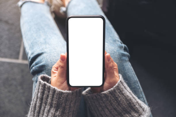 top view mockup image of a woman holding black mobile phone with blank desktop screen while sitting on the floor - phone, travelling, copy space imagens e fotografias de stock