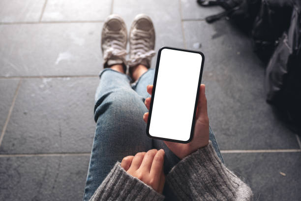 top view mockup image of a woman holding black mobile phone with blank desktop screen while sitting on the floor with baggage - phone, travelling, copy space imagens e fotografias de stock