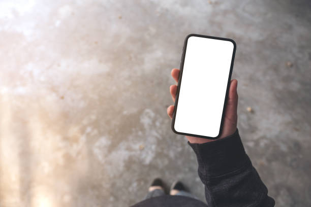 Das Mockup-Bild einer Frau, die ein schwarzes Handy mit leerem Desktop-Bildschirm hält, während sie auf Beton steht, ist ein Bild in der obersten Ansicht. – Foto