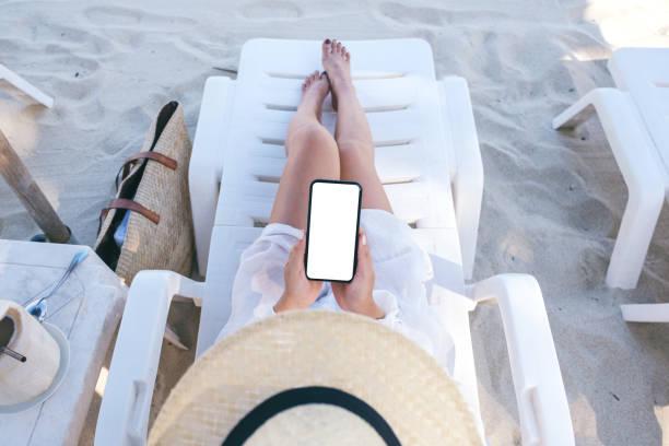 Top-Ansicht Mockup-Bild einer Frau hält weißes Handy mit leerem Desktop-Bildschirm, während sie sich auf Strandkorb am Strand legt – Foto