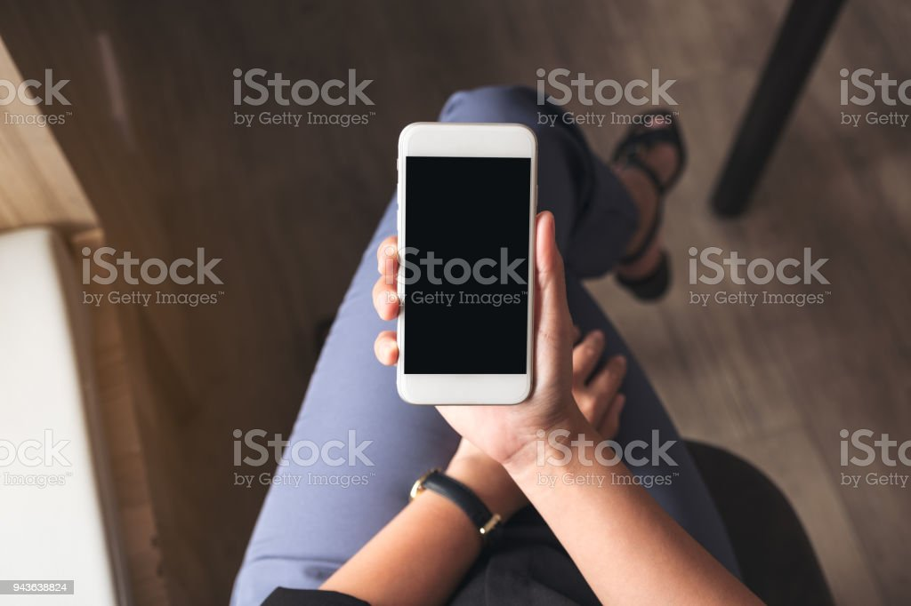 Top view mockup image of a woman holding white mobile phone with blank black desktop screen on thigh in cafe royalty-free stock photo