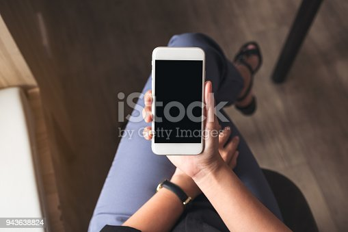istock Top view mockup image of a woman holding white mobile phone with blank black desktop screen on thigh in cafe 943638824