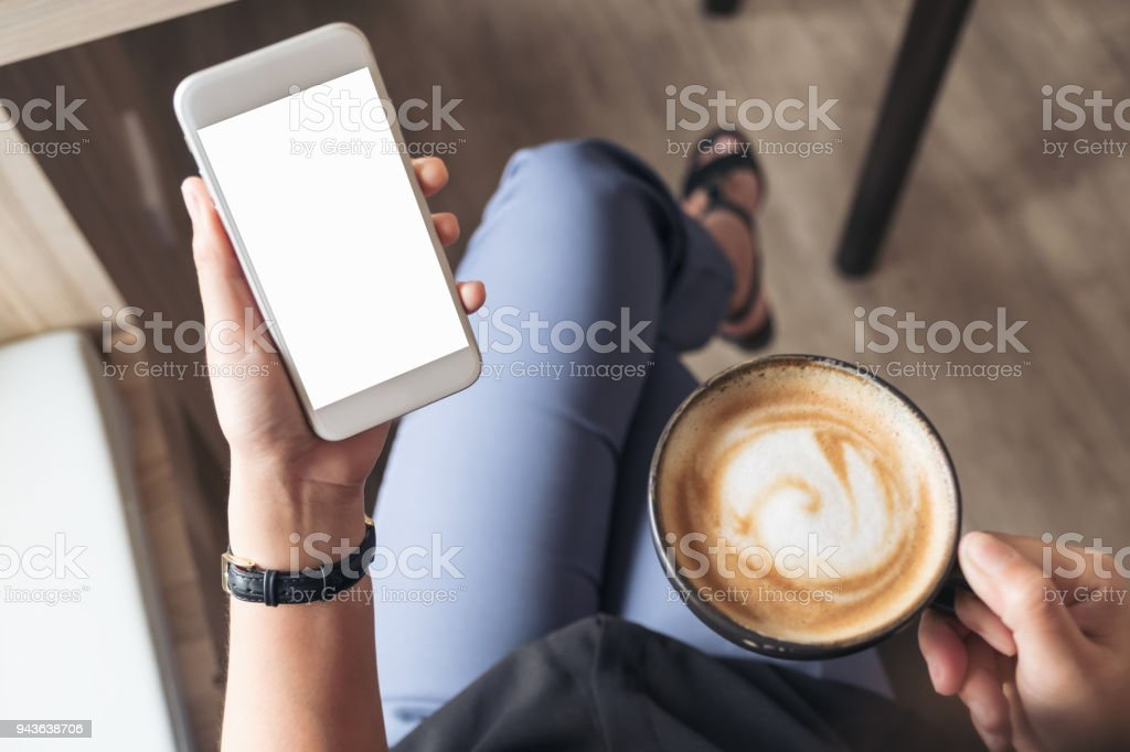 Top view mockup image of a woman's hand holding white mobile phone with blank desktop screen while drinking coffee in cafe stock photo