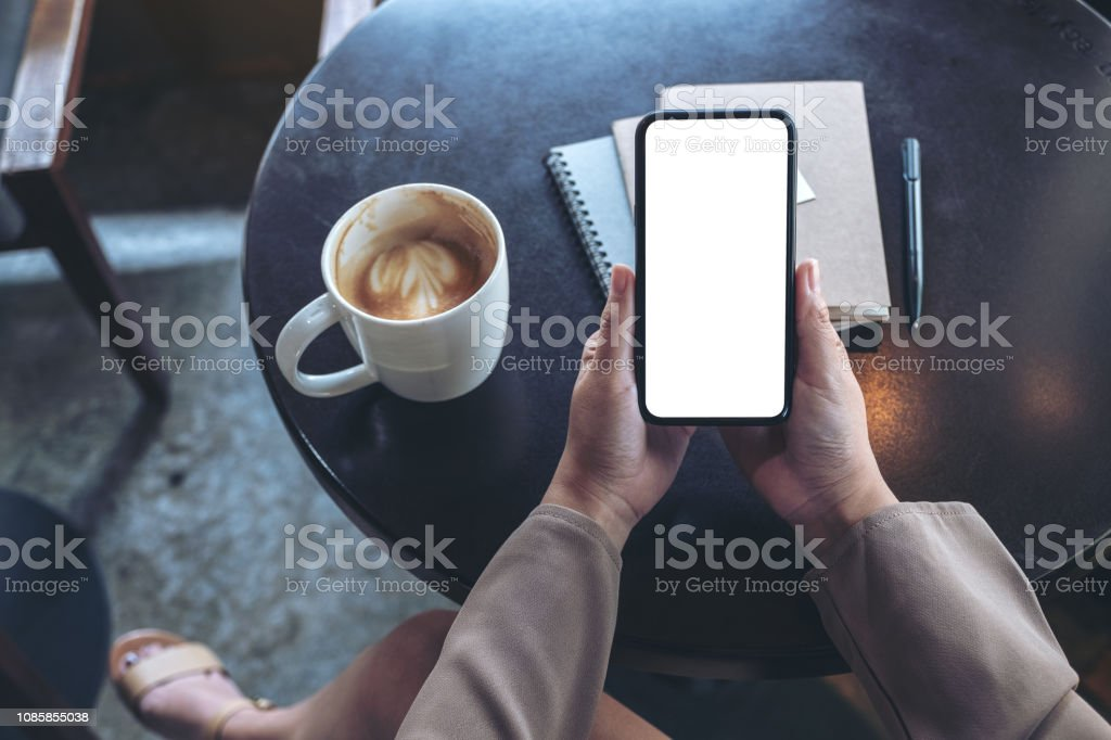 Top view mockup image of woman holding black mobile phone with blank...
