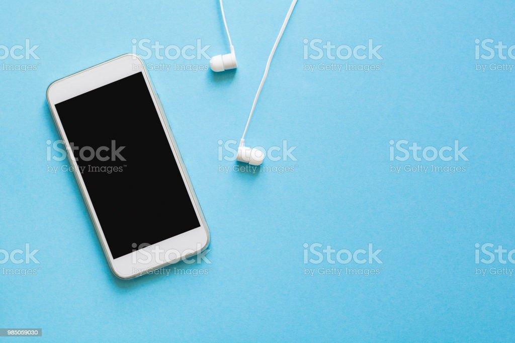 Smartphone de maquette vue de dessus et écouteurs sur fond bleu. Poser de plat. Espace pour copie photo libre de droits