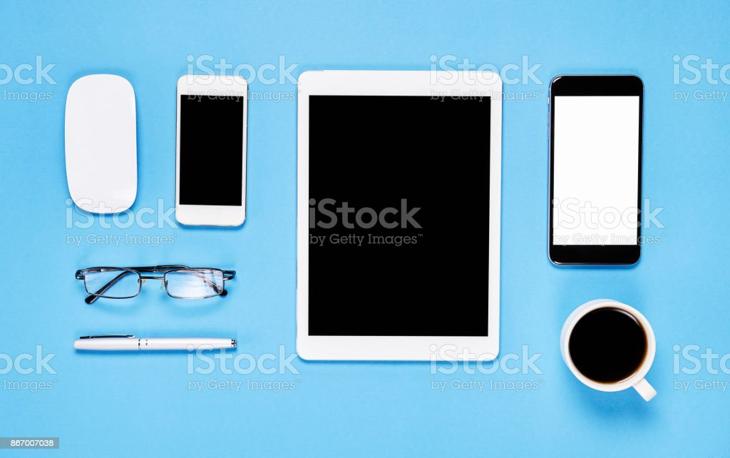 Top view, Modern workplace with laptop and tablet with smart phone placed on a pastel yellow background. Copy space suitable for use in graphics. stock photo