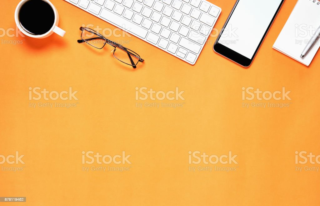 Top view, Modern workplace with laptop and tablet with smart phone placed on a pastel Orange background. Copy space suitable for use in graphics. stock photo