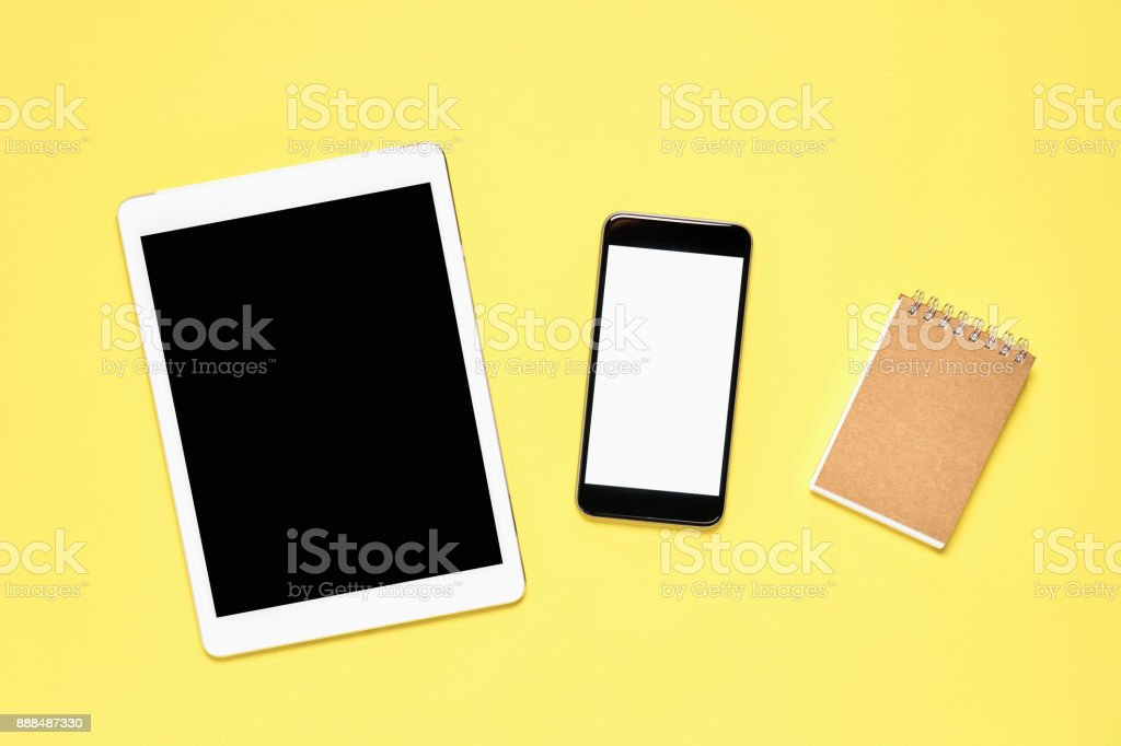 Top view, Modern workplace with Notebook and tablet with smart phone placed on a pastel yellow background. Copy space suitable for use in graphics. stock photo