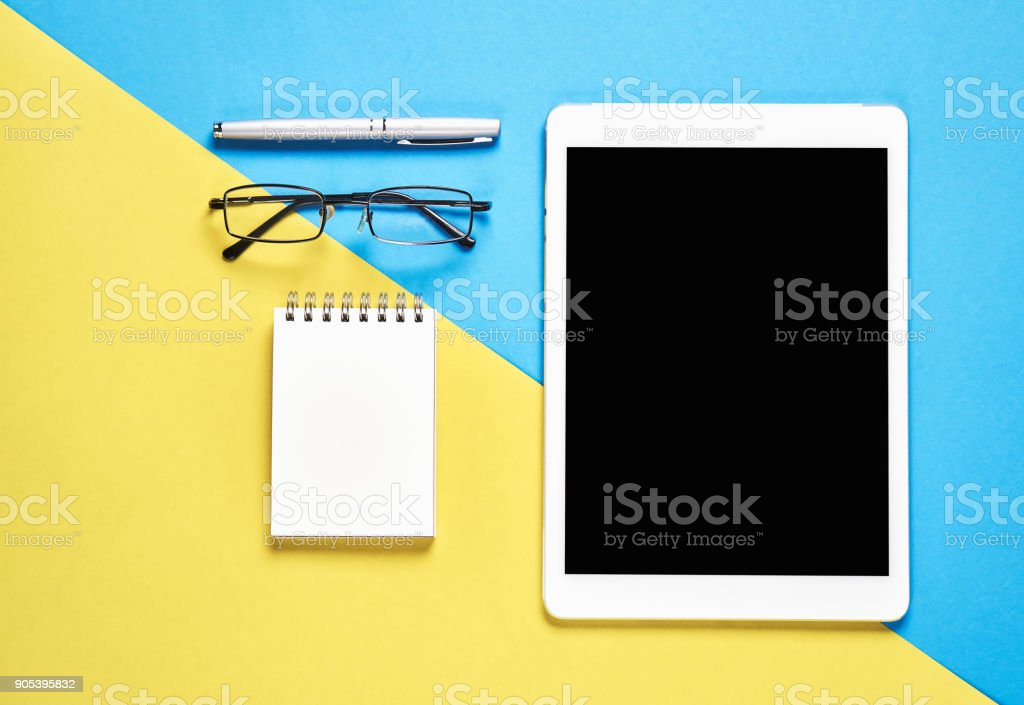 Top view, Modern workplace with tablet placed on a pastel yellow background. Copy space suitable for use in graphics. stock photo