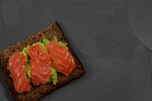Top view multi-cereal bread toast with smash avocado and red fish salmon on concrete