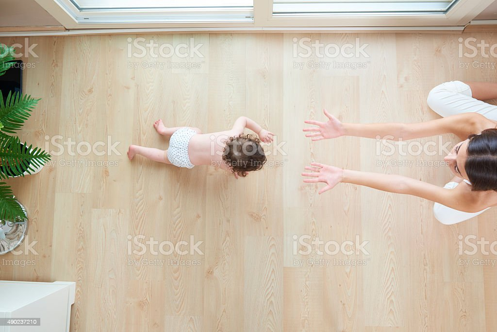 Top view of a baby crawling toward mother stock photo