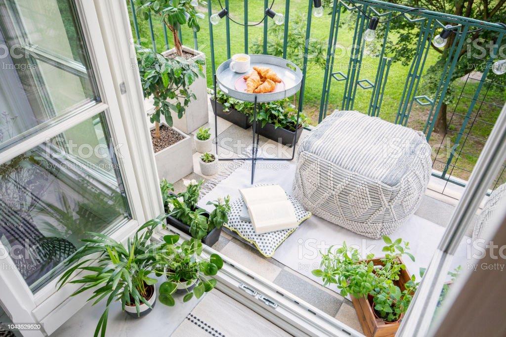 Vista superior de un balcón con plantas, Puf Mesa con desayuno - Foto de stock de Acogedor libre de derechos