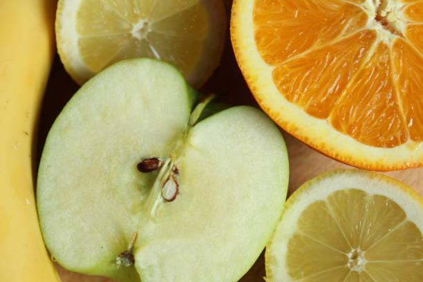 Top view of a banana, sliced lemon and half of orange and apple stock photo