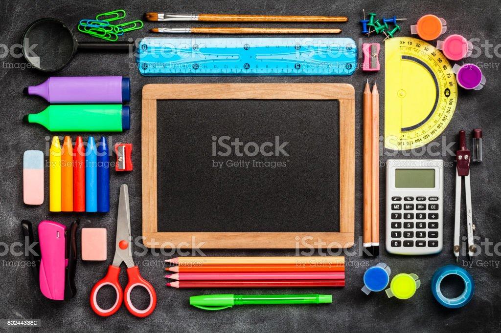 Draufsicht auf eine Tafel mit Schule liefert auf schwarzem Hintergrund – Foto