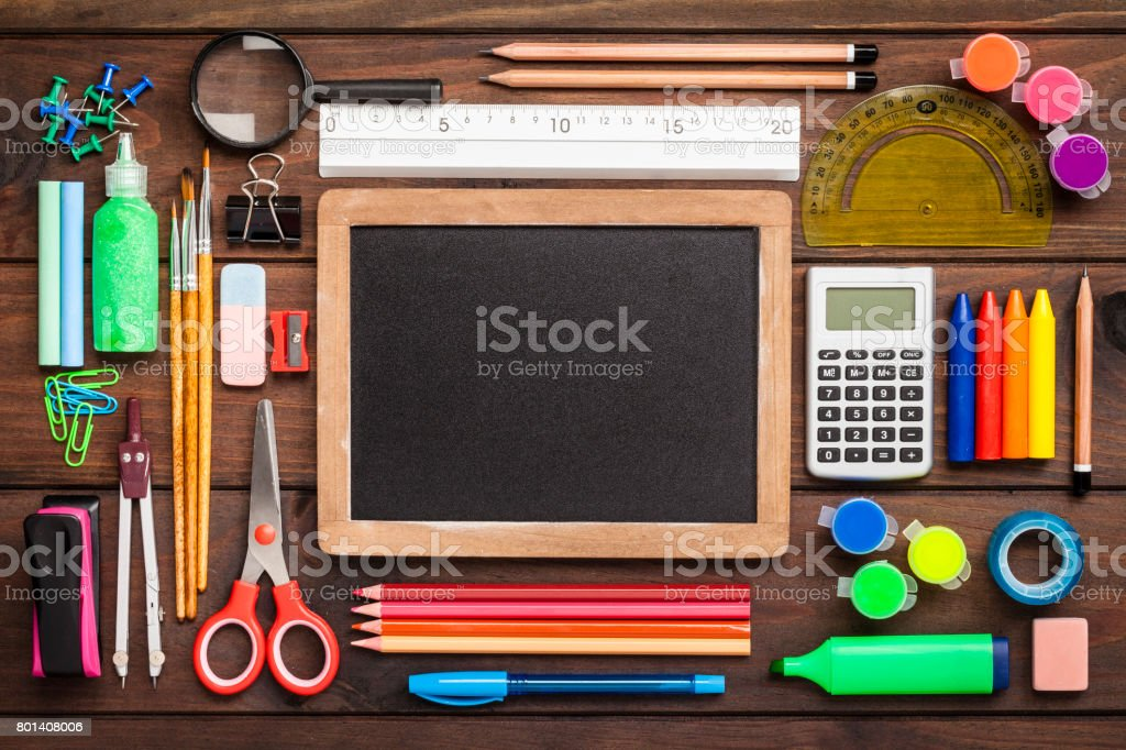 Top view of a blackboard with school supplies on wooden table stock photo