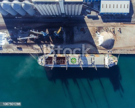 Top view of a bulker with an open empty hold. Aerial view to unload the cargo ship.