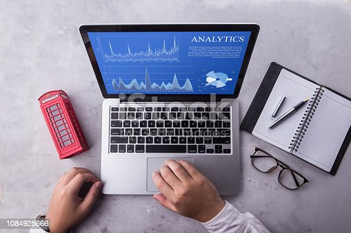 istock Top view of a businessman laptop computer with analytics data concept on screen. Working with financial graphs charts, using business software for data analysis and project management concept 1084925666